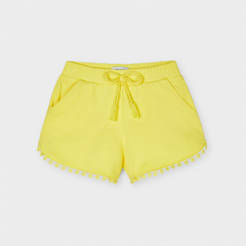 Pantalón corto de tipo short para niña. Cintura elástica con cordón ajustable. Cómodo tejido de punto. Diseño con detalles en el bajo al tono. Elementos de adorno: borlas.