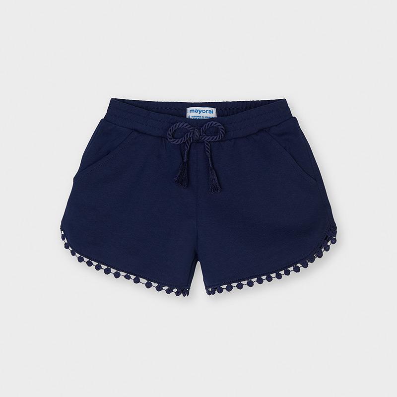 Pantalón corto de tipo short para niña. Cintura elástica con cordón ajustable. Cómodo tejido de punto. Diseño con detalles en el bajo al tono. Elementos de adorno: borlas. Disponible en colores.