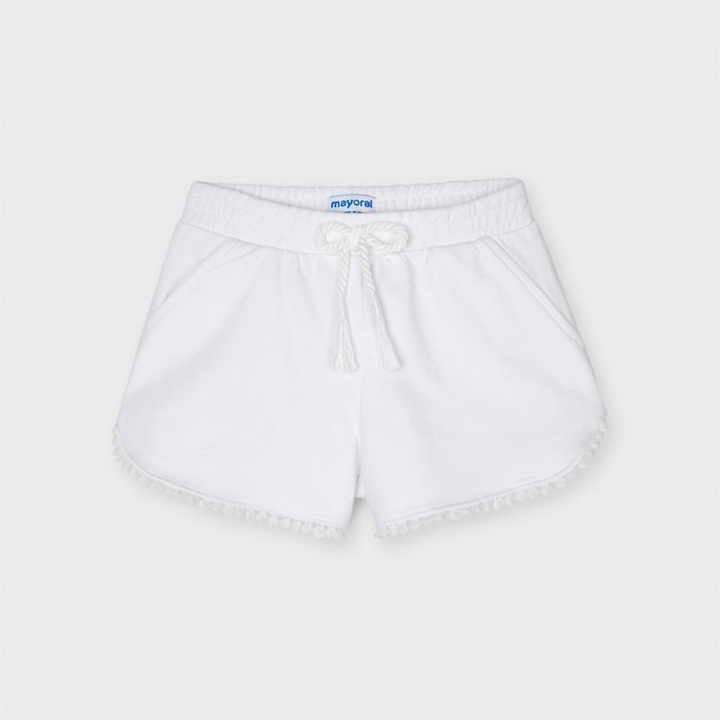 Pantalón corto de tipo short para niña. Cintura elástica con cordón ajustable. Cómodo tejido de punto. Diseño con detalles en el bajo al tono. Elementos de adorno: borlas