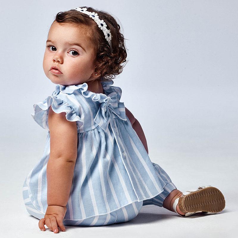 Blusón de manga corta para bebé niña de 6 a 36 meses con detalles de volantes. Cuello redondo con volante. Cierre con botones en la espalda para facilitar la puesta de la prenda. Mezcla de tejidos combinados para lograr un diseño único y diferente. Modelo con rizo. Elementos de adorno: aplique de lazo.