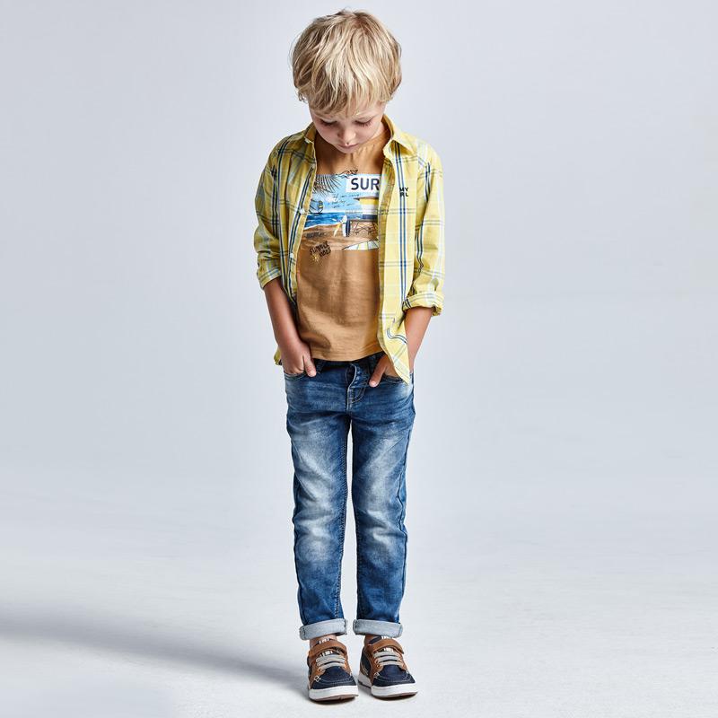 Prenda ECOFRIENDS contiene poliester reciclado. Pantalón largo para niño de 2 a 9 años, de corte ajustado (Slim fit) que se adapta a la silueta. Cierre con botón a presión en la parte delantera y goma elástica regulable en la cintura para ajustar el talle. Vaquero muy cómodo y blandito.