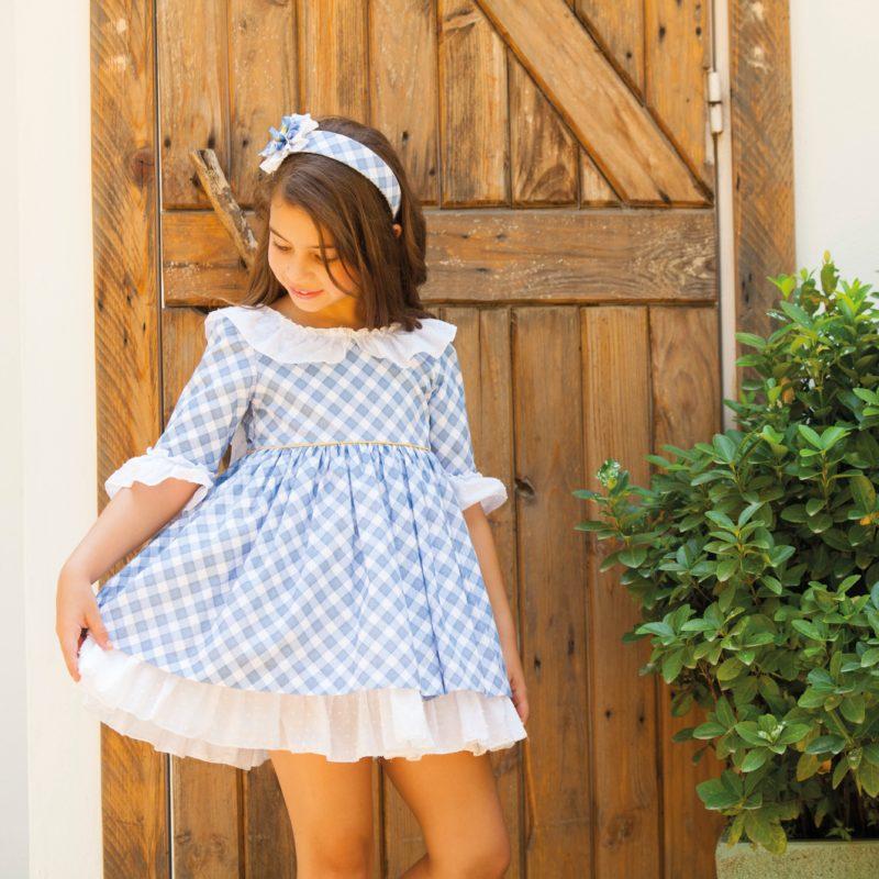 Cuadro vichy en azul, corte en cintura, volante en blanco en manga y cuello. Bajo del vestido en blanco.