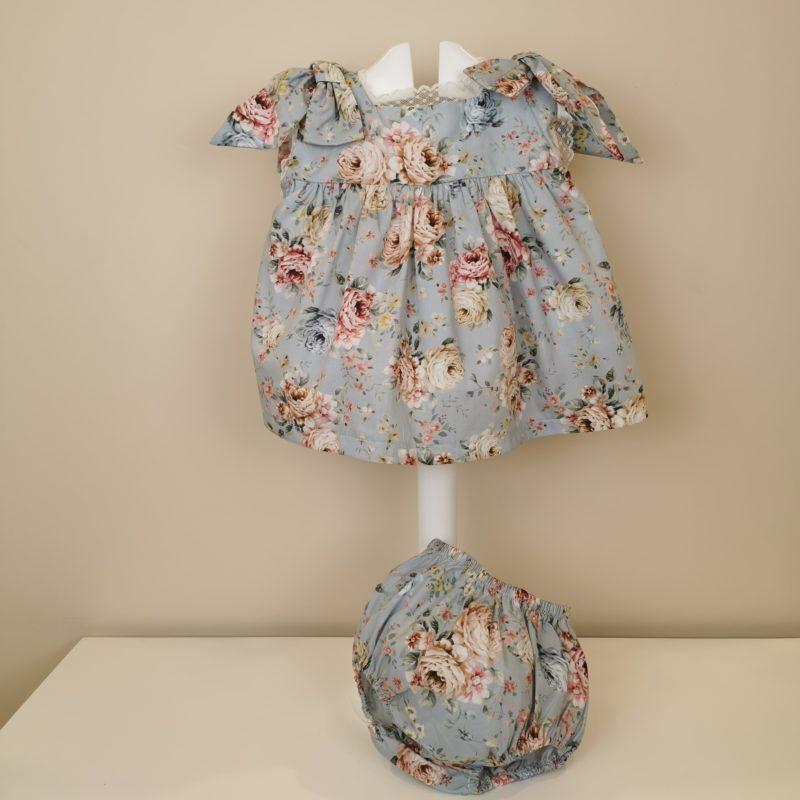 Vestido con estampado de flores fondo azul empolvado, manga sisa,lazadas en hombros. Puntilla estrechita en mangas y cuello. Espalda pico con puntilla ,cruzado con botón. Braguita con goma en cintura y piernas.