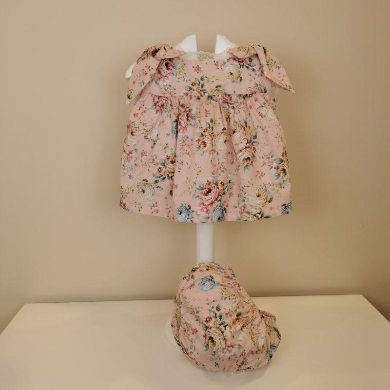 Vestido con estampado de flores fondo rosa empolvado, manga sisa,lazadas en hombros. Puntilla estrechita en mangas y cuello. Espalda pico con puntilla ,cruzado con botón. Braguita con goma en cintura y piernas.
