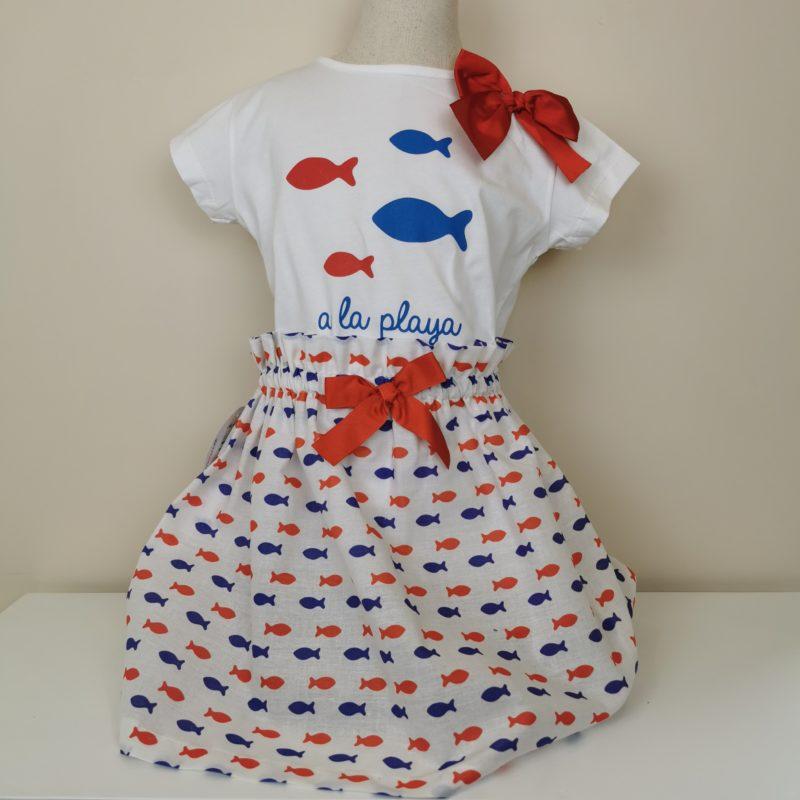 Conjunto de camiseta con motivos de impresión de peces en rojo y azul, lazada en lateral. Falda con estampación de peces, goma en cintura y lazo en rojo. Un conjunto fresco y alegre.