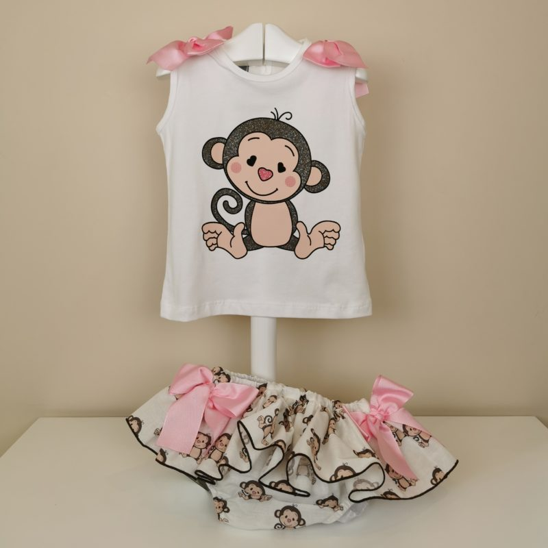 Camiseta blanca manga sisa,monito con detalle de purpurina,lazos en hombros. Braguita con estampado,volante ribeteado en marron, lazadas laterales en rosa.